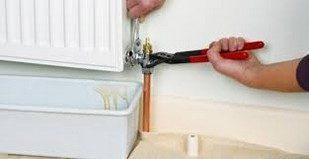Un plombier qui répare un radiateur